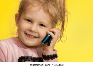 Little girl on the yellow background is speaking over the mobile