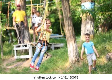 Little girl on zip line in adventure park. Summer camp