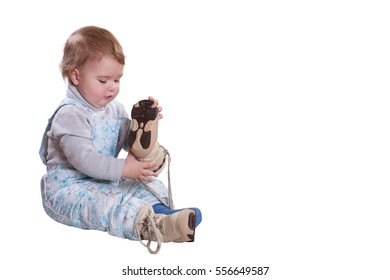 Little girl one year wearing overalls and a knitted sweater, hat and winter boots with fur, isolated on white background. Winter clothes.