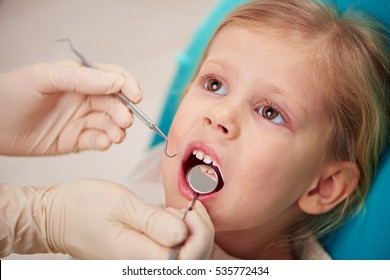 Little girl with open mouth curing teeth in dental clinic. Doctor in gloves with dental tools examining kid's mouth.