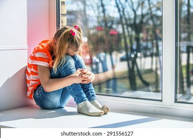 Little girl in orange blouse sits on a window sill, crying.