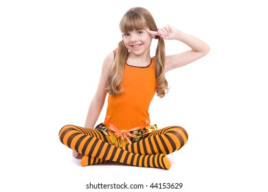 Little girl in the orange dress with finger near her head is sitting on the floor. Portrait of an attractive young teenager is  playing the fool and smiling in orange over white background.