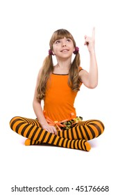 Little girl in the orange dress is sitting on the floor and pointing to up. Portrait of an attractive young teenager is smiling in orange over white background.