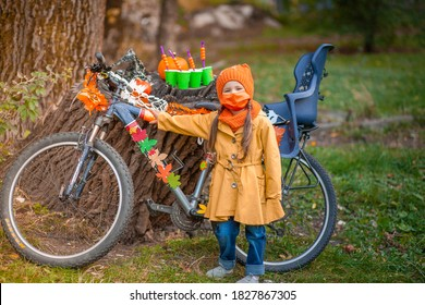 A little girl in an orange protective mask stands near a bicycle decorated with orange leaves and garlands on the eve of Halloween, a child holds a green paper cup with a straw with plastic pumpkins.