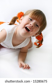 Little girl in an orange shorts wriggles and poses the isolated background
