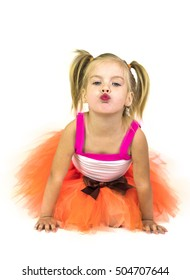 Little girl in orange skirt tutu with brown bow isolated on white background. Little girl