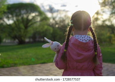 little girl outdoors alone with a toy, without parents, social