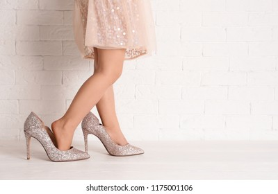 Little girl in oversized shoes near brick wall with space for text, closeup on legs