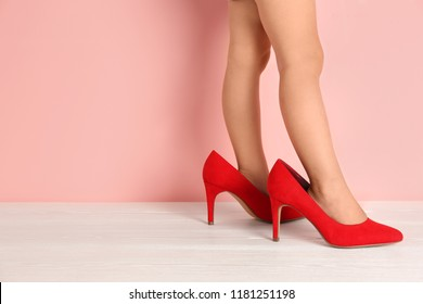 Little girl in oversized shoes near color wall with space for text, closeup on legs