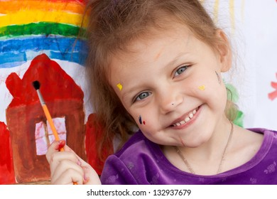 little girl with paint brush and painting