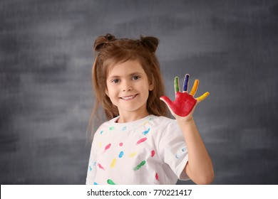 Little girl with painted hand on grey background