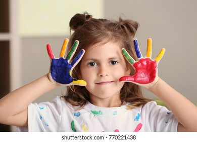Little girl with painted hands indoors