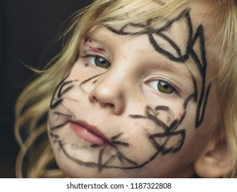 The little girl painted her face with a marker. Makeup for Halloween.