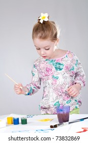 Little girl painting with brush