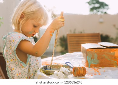 Little girl painting a cardbox with paints sitting outdoors in t