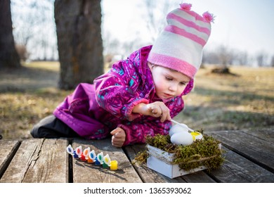 Сute little girl painting eggs for Easter in the garden.Early learning concept. Easter outdoor activities for kids. Country side Easter.