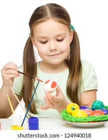 Little girl is painting eggs preparing for Easter, isolated over white