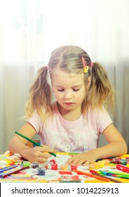Little girl is painting with gouache. Happy little girl painting in at her home. Close up, selective focus.
