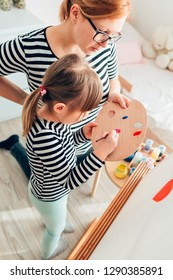 Little girl painting with her mother using easel stand at home