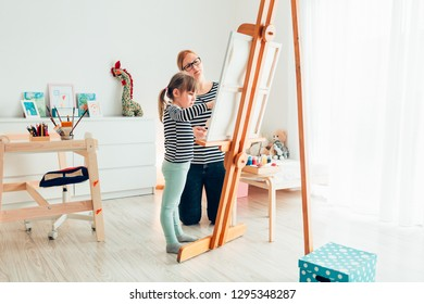 Little girl painting with her mother using easel stand at home with copy space