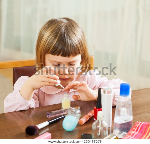 Little girl painting her nails on the hands