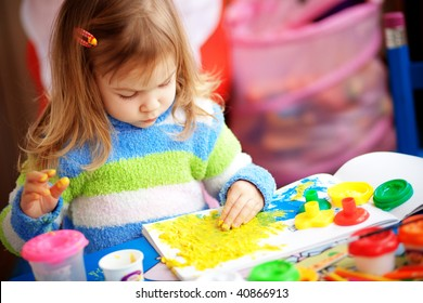 Little girl painting in her nursery at home