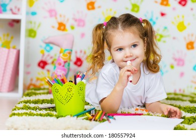 Little girl painting in her room at home