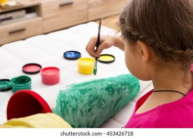 A little girl painting her school cornet