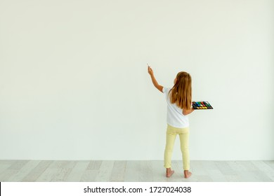 Little girl painting on white wall indoors. view from the back