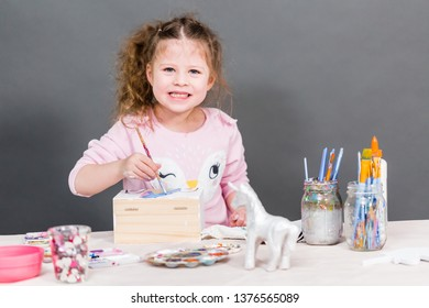 Little girl painting a unicorn on a wood box with acrylic paint.