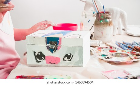 Little girl painting a white unicorn with acrylic paint on a wooden box.