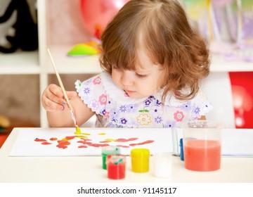little girl paints paints