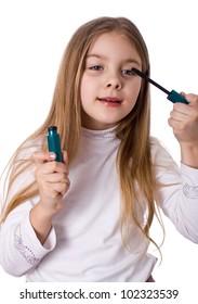little girl paints the eyelashes mascara. Isolated on white background