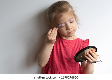 little girl paints her eyes, stands in a red dress