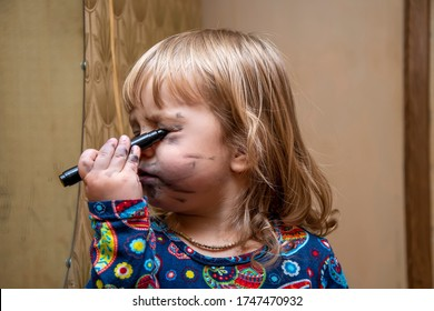 A little girl paints her face with a felt-tip pen in front of a mirror, a young makeup artist. Concept: childlike spontaneity, the desire to be an adult and beautiful, make-up with your own hands.