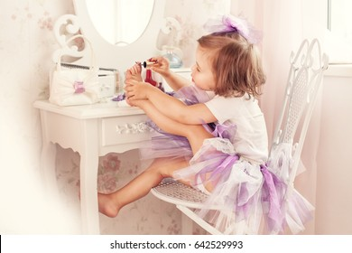 A little girl paints her nails. She is in my mother's bedroom, sitting near the mirror.