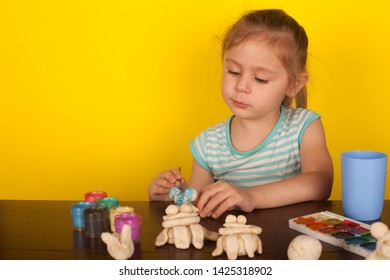 Little girl paints toy animals paints on a yellow background