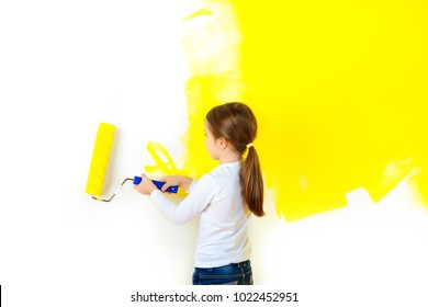 little girl paints the walls with a roller in the room