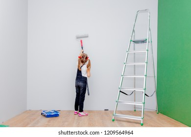 little girl paints the walls in the room with a roller. The concept of repair in the apartment