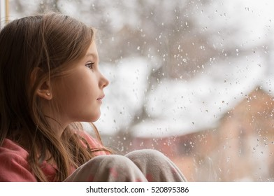 little girl in pajamas looking out the window at the first snow