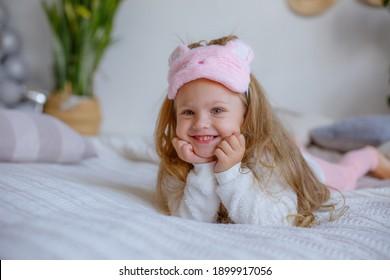 little girl in pajamas lying on the bedroom