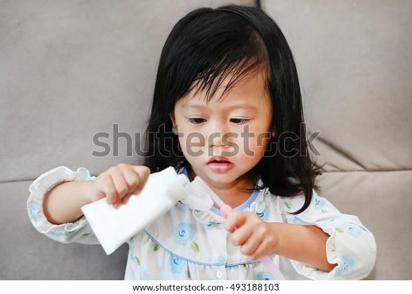 Little girl in pajamas on sofa brushing teeth