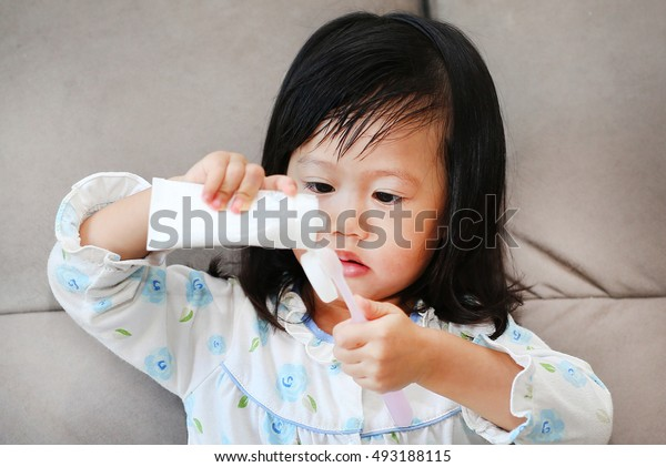 Little girl in pajamas on sofa squeeze toothpaste for brushing teeth.