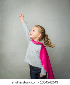 Little girl paly superhero in a pink cloak