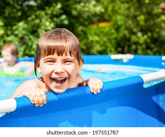 Little girl palying in a swimming pool at a summer garden