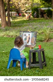 little girl in the park draws with paints