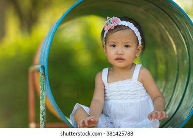 little girl in the park with playground