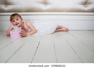 Little girl in a party dress, laying on the floor with a present
