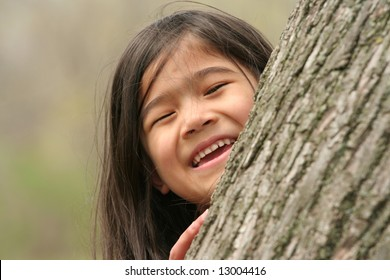 Little girl peeking out from behind a tree
