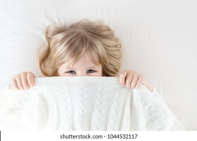 Little girl peeking out blanket on bed. Cute kid smiling and hiding under knitted cover. Palyful and mischievous eyes. Hide-and-seek. Children having fun playing active games. Happy childhood concept